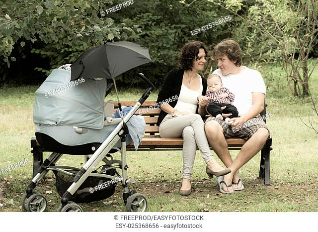 Happy mother and father with baby in park, France