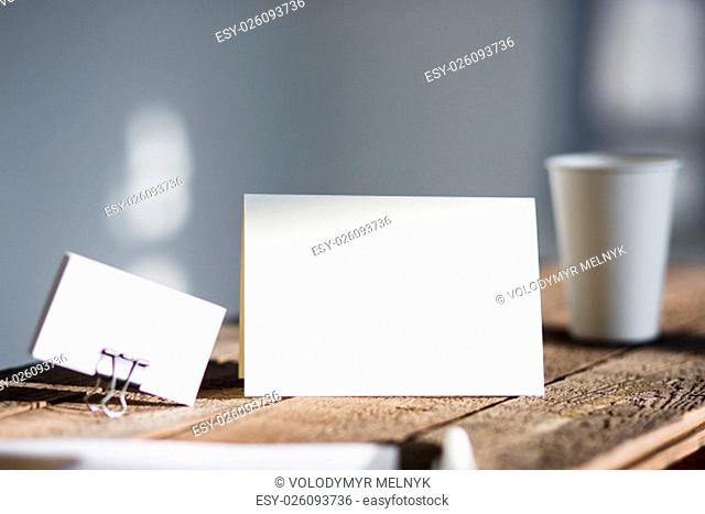 Blank invitation greetings card to replace your design on gray wooden table