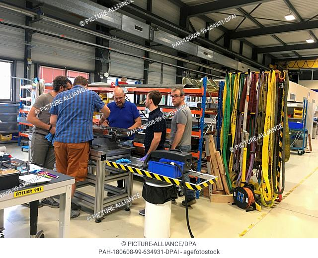 28 May 2018, France,Prévessin: Workers standing in a workshop of the European Organization for Nuclear Research (CERN). The foundation stone for an extension...