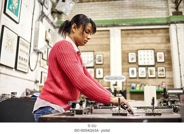 Mid adult woman using squeegee on screen printer in traditional print workshop
