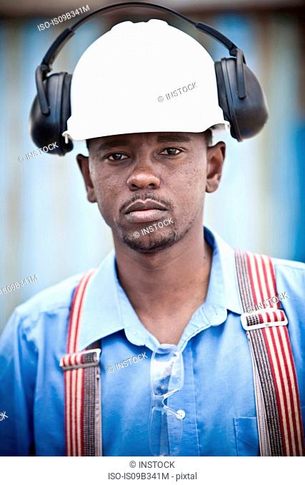 Portrait of male worker in hard hat at recycling plant