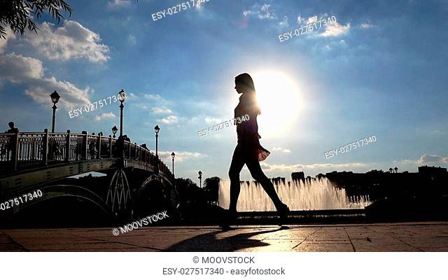 Silhouette of a slim girl in high heels walking on park embankment
