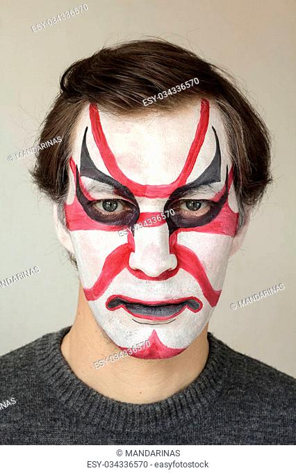 Severe man with face painting kabuki black red and white color