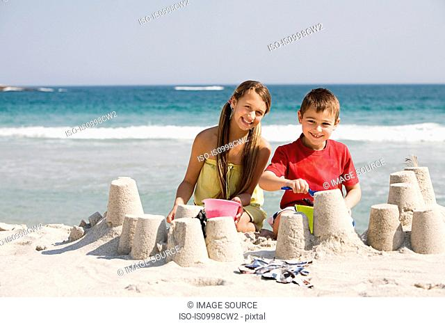 Girl and boy making sandcastles on the beach