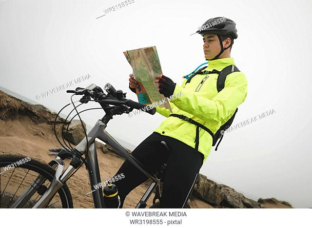 Man with cycle reading map at the beach