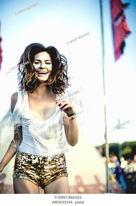 Young woman at a summer music festival wearing golden sequinned hot pants, face painted, smiling at camera