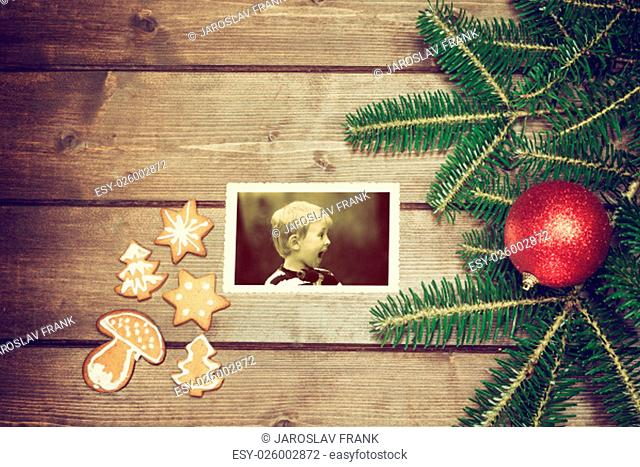 Vintage aerial view of the symbols of the Christmas on the wooden desk. The Christmas gingerbread is in the left side. On the old k photo is side view of the...
