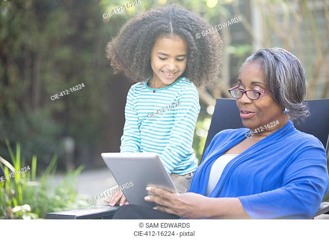 Grandmother and granddaughter using digital tablet outdoors