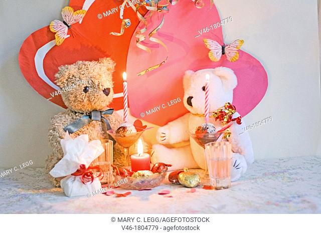 RagTag Teddy Bear has a present for White Teddy Bear  Curly-haired brown teddy bear with a blue ribbon sits with a white teddy bear with gold and red ribbon...