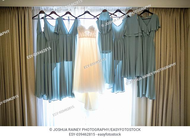 Wedding dress of the bride hanging with some dresses for the bridesmaids before a California ceremony