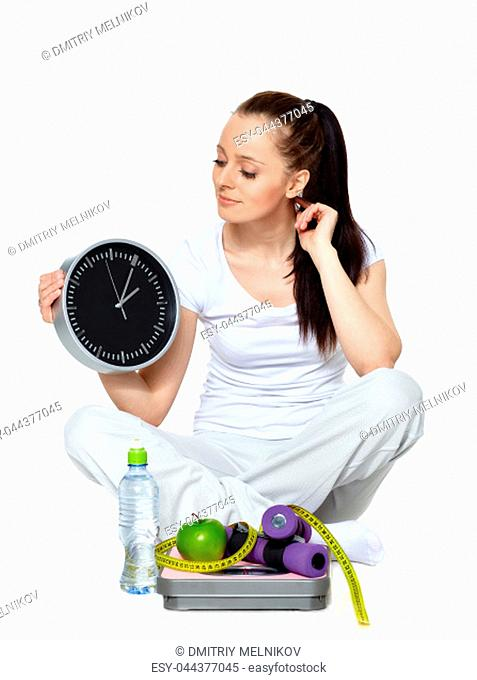 Sporty young woman with clock, scales, dumbbells and apple on a white background. Time for slimming