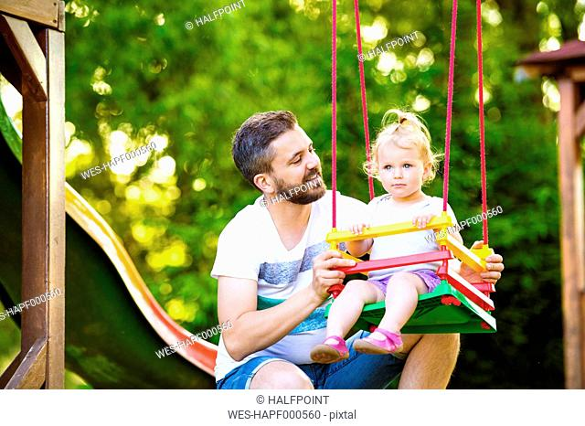 Father looking at his little daughter sitting on a swing of playground