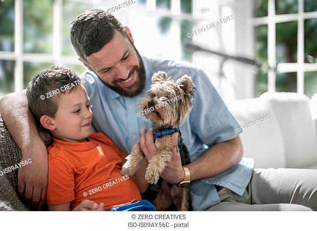 Father and son with pet dog on sofa