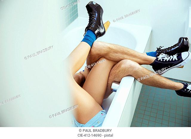 Couple's legs intertwined in bathtub