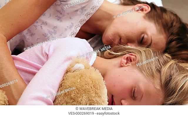 Mother and daughter sleeping together in bed