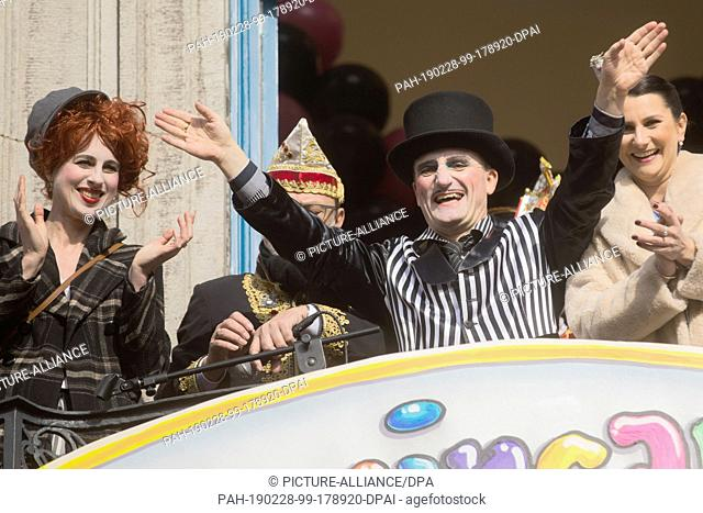 28 February 2019, North Rhine-Westphalia, Düsseldorf: Thomas Geisel (SPD), Lord Mayor, waves disguised next to his wife Vera (l) from the balcony of the town...