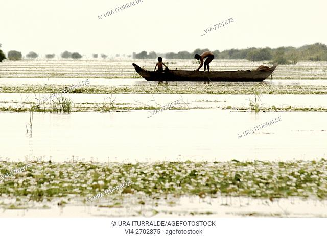 Father and son fishing with his small boat on the Mekong river, Cambodia