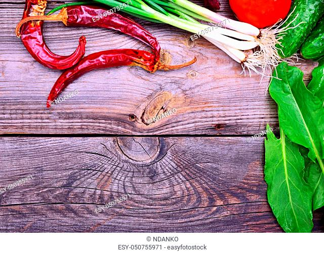Red chili, green onions and other vegetables on a gray wooden surface, empty space in the middle