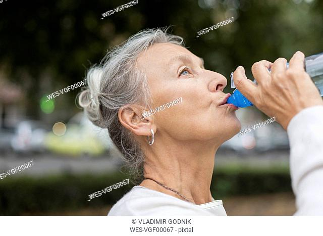 Senior woman outdoors drinking water from bottle