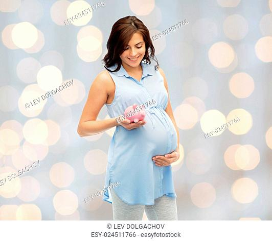 pregnancy, motherhood, finance, saving and people concept - happy pregnant woman with piggybank over holidays lights background