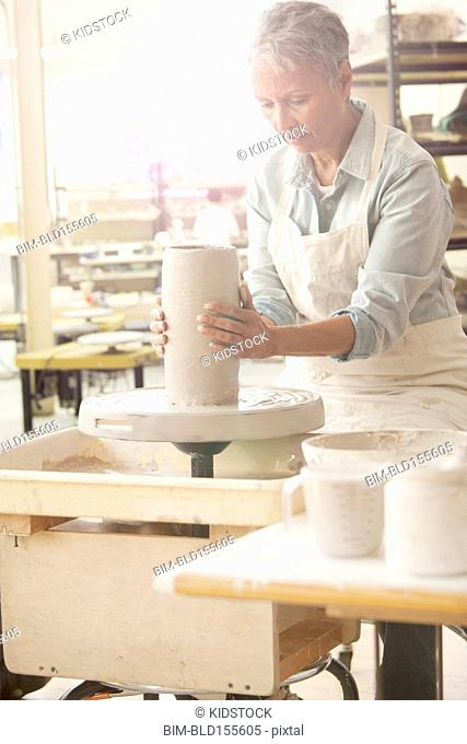 Older African American woman forming pottery on wheel in studio
