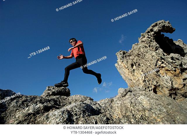 Man running and jumping over rocky terrain