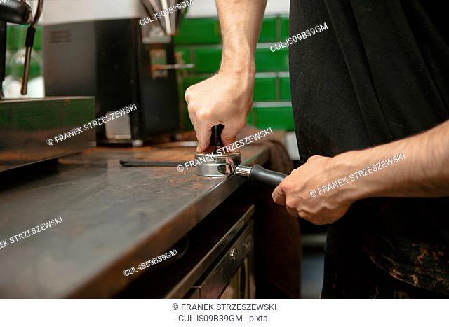 Male barista's hands preparing coffee machine in cafe