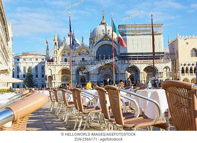Alfresco seating tourists and west facade of St Mark's Basilica in Piazza San Marco, Venice, Veneto, Italy, Europe
