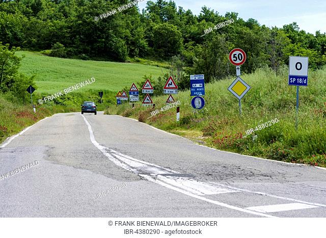Road flanked bei many traffic signs, Castiglione d'Orcia, Val d'Orcia, Tuscany, Italy