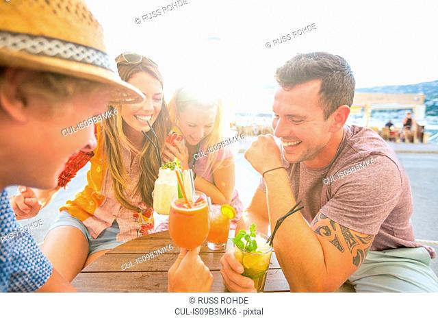 Two adult couples laughing over cocktails at waterfront restaurant, Majorca, Spain