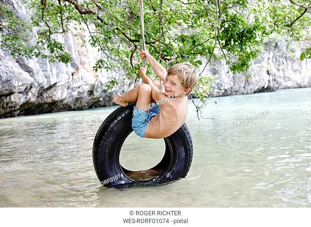 Thailand, Ko Yao Noi, Phang Nga Bay, happy boy swinging on tire above the sea