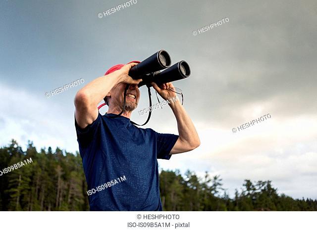 Senior man looking through binoculars toward coast of Maine, USA