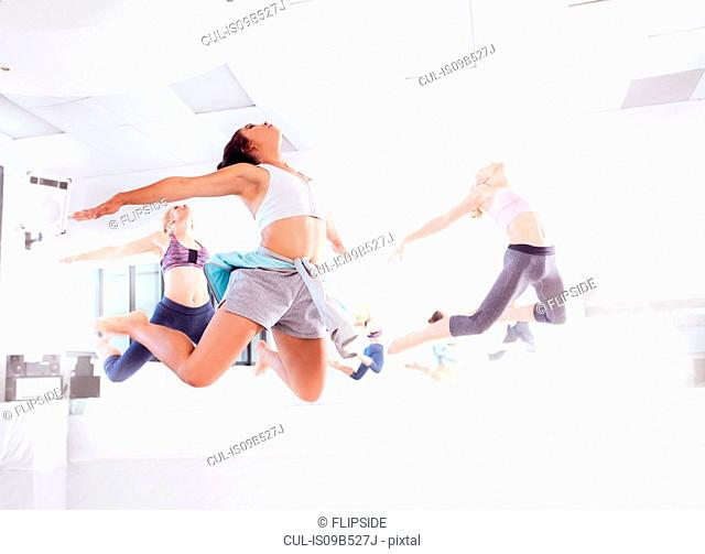 Young female ballet dancers practicing in dance studio, jumping in unison