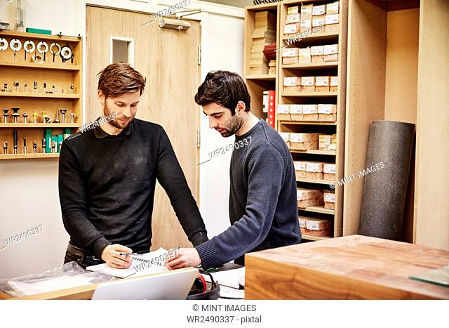 A furniture workshop making bespoke contemporary furniture pieces using traditional skills in modern design. Two people discussing a design