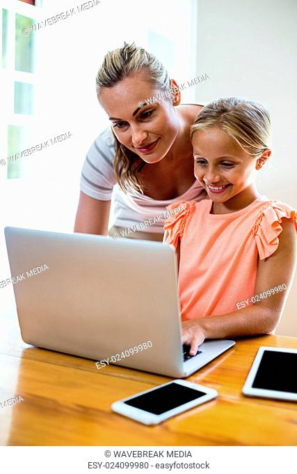 Mother assisting daughter in uising laptop at home