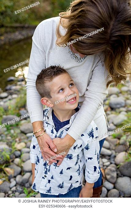 Lifestyle portrait of a young boy and his mother along the banks of the McKenzie River in Oregon