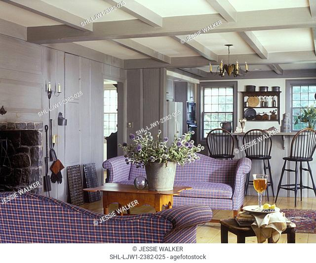 LIVING ROOMS - Clean Country Living style, exposed beams, gray wood paneling, plaid sofas, kitchen in background, counter with Windsor back bar chairs