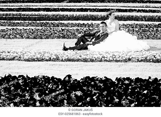 The bride and groom sitting on a lawn with flowers while the groom is looking at the camera and the bride is looking away