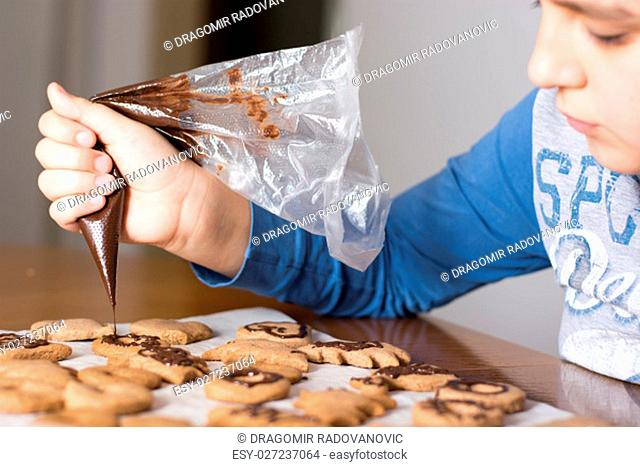 New year and happy family concept. Kid making decoration on gingerbread cookie close up. Baking with children