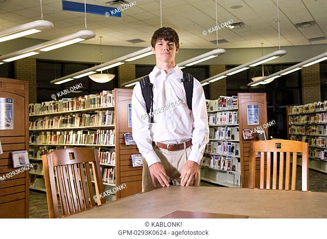 Portrait of teenage student at table in library
