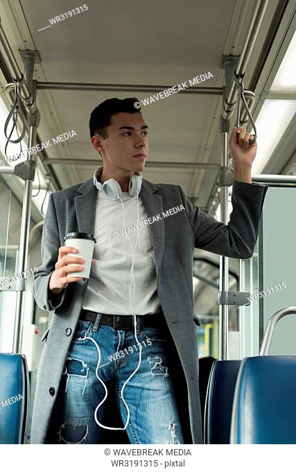 Man with coffee cup standing in the bus
