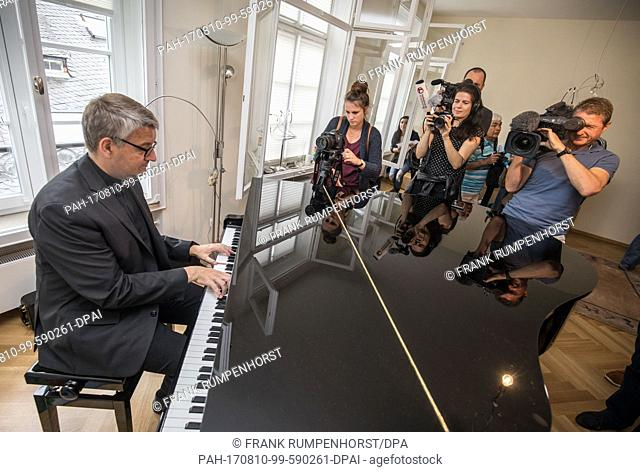The appointed bishop of Mainz, Peter Kohlgraf (L), playing a short song on his piano in his new address at the Domgasse street in Mainz, Germany, 10 August 2017