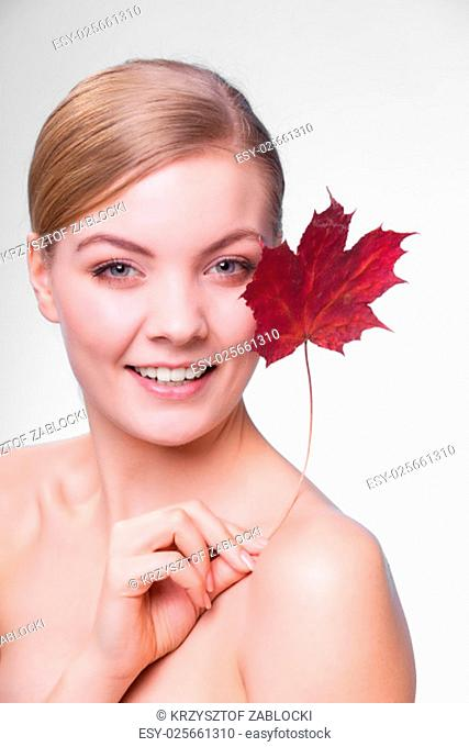 skincare habits. portrait of young woman with leaf as a symbol of red capillary skin on gray. face of girl taking care of her dry complexion