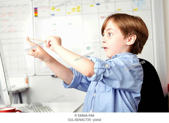 Boy playing with elastic band in office