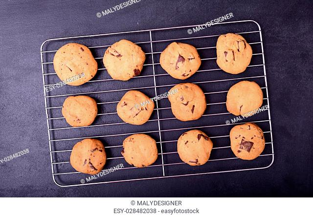 Home baked chocolate cookies on cooling rack on black background