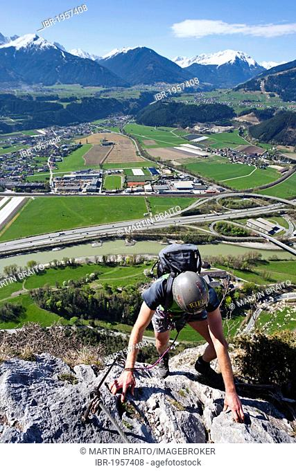 Mountain climber ascending the Kaiser Max climbing route on Martinswand near Innsbruck, looking over the Inntal Valley and Kematen, North Tyrol, Tyrol, Italy