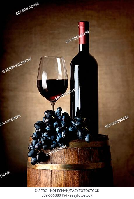 Bottle of red wine, wine glass, grapes and wooden barrel