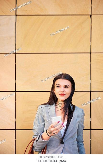 Businesswoman outdoors, using smartphone