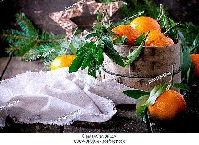 Tangerines with leaves in vintage sieve with Christmas tree and dry orange on white textile rag over old wooden table. Dark rustic style. Side view