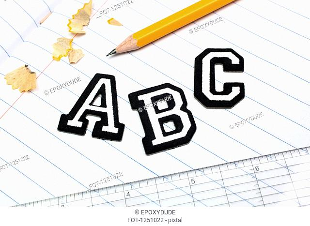 Varsity font stickers spelling out A, B, C atop a lined paper notebook with ruler and pencil